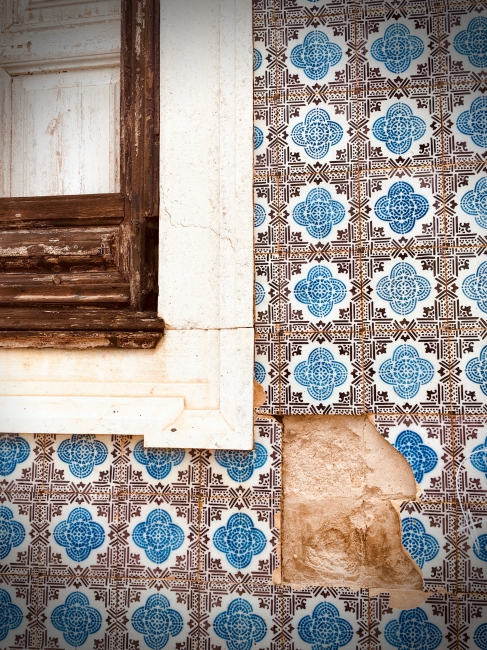 Missing tiles from black and blue tiled wall